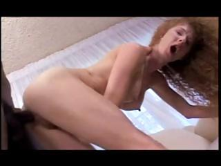 Curly-haired redhead with a fine set of tits gets fucked by dark guy