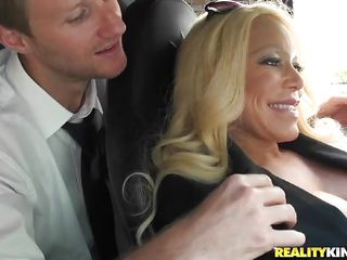 Alexis was in a party and some excited guys can't take their messy eyes off from this hot breasty blonde. They wanted to bang this milf so badly that one of 'em seduced her and started making out with her in the car! See how that guy made her taking out that large boobs and enjoyed groping 'em softly!