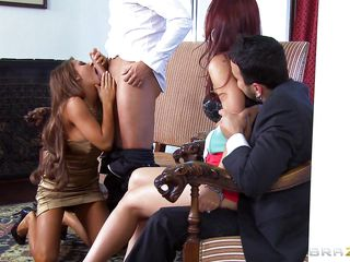 At dinning table husband tells some truth about himself, redhead wife doesn't like it and wants to leave that place. As she is going to leave she is caught by one more sexy blonde babe, husband tells her to teach her wife a lesson. That honey lay her on the sofa and fingers her pussy and kisses her erotically. Blonde hottie unzips her husband pant and pulls of his hard dick and starts engulfing it in front of her husband while she is held tight by one more man.