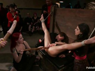 Trapped in a bondage device with her legs widen wide and her head secured, Jiz Lee is licking the cunt of a smoking hot dark brown and get's fucked in her wet pussy by a dildo that is handled by the girls standing in line to have joy with her fastened body. These bitches are humiliating her and surely won't stop soon.