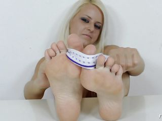 sexy flaxen-haired babe giving feet deception to a dildo.
