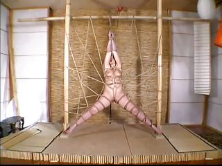 This sexy woman is bent over the table and they are not going o allow her to move or do anything else as they secure her body with the help of ropes tying her up in a spreadeagled position with her eyes and legs wide open. as the reporter shows various implements hanging from the wall.