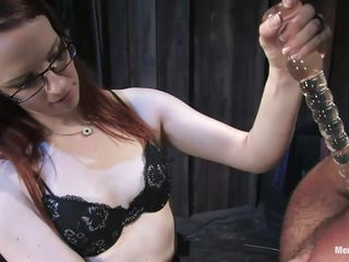Claire Adams is a sexy ginger milf who has her chap tied and upside down. He's wrapped in some kind of cloth. She fucks his wazoo with a sextoy by hand, then spanks him. Pretty soon she's hitting him with a leather crop and pulling his hair, making him cry out. She begins cutting him free for what's next.