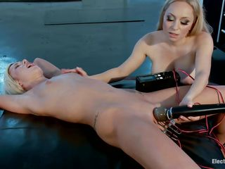 Having no one around for a fast fuck, a blonde milf with large love bubbles ties up her glamorous female friend. The sex domina then hangs electrodes on her muff and begins to rub on Maia Davis's young shaved pussy with a vibrator. After attaching a mouth ding-dong to her, she begins slamming her muff against it.