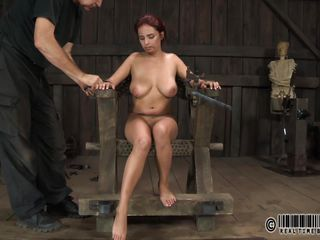 Ashley Graham is tied up in shackles with a milking machine attached to her massive breasts. This babe a dirty whore and these men punish her with humiliating tasks. She's tied to her chair so you can get a more good look at her massive melons.