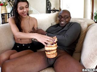 Brunette woman, with a box full of doughnuts is playing with a black man's cock. That babe puts some doughnuts over his dick, making it sweeter, then she begins to engulf his dick. Then she has her cum-hole licked.