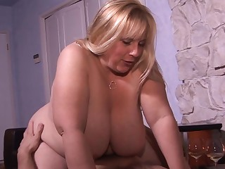 A fat woman that has huge bosom and a chubby belly is getting fucked