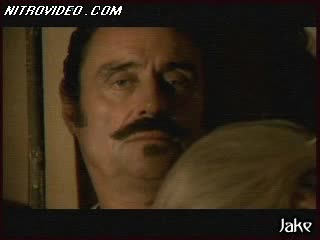 Topless Paula Malcomson Lying in Bed with a Moustached Man