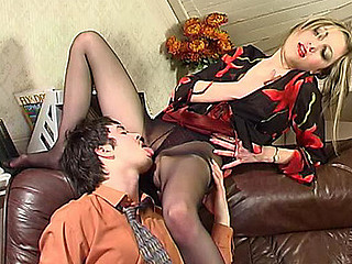 Female co-worker in black pantyhose begins her working day with giving footjob