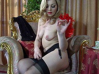 Golden-haired temptress peels off her red negligee and puts on stylish black stockings