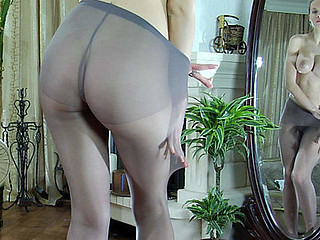 Leggy playgirl posing topless by the mirror in constricted fitting gray pantyhose