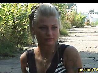 Hawt blond makes water on asphalt