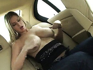Carol plays with her massive jugs in the back seat of a car.