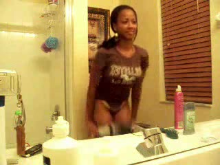 Cute youthful ebony gal does a hot striptease in front of her washroom mirror, and shows off her ideal tits.