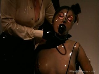 Golden-haired Femdom-goddess Makes Busty Obedient Brunette Wear Suffocating Latex Suit