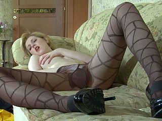 Sexed-up vixen slips a hand underneath her thin black hose with a print